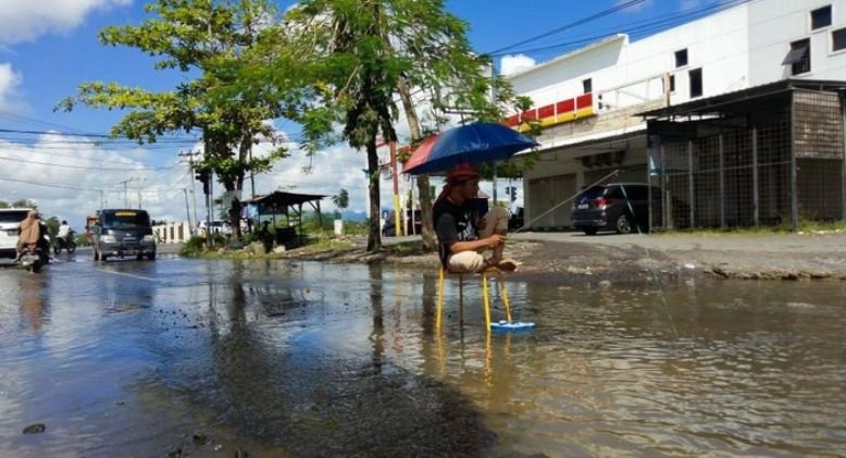 Protestor Takes Bath and Fishes in Large Pothole, Authorities Finally Repair Road